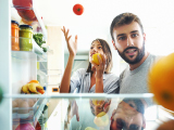 couple looking inside refrigerator