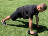 trainer doing pushup with dumbbells