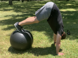 trainer doing pike on stability ball