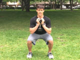 trainer squatting with dumbbell