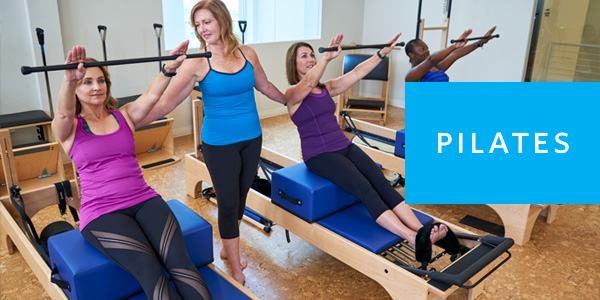 Small group Pilates class with three women on reformers taught by Pilates instructor